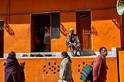 People walking in front of an orange building during the Hindu Festival of Maha Kumbh Mela Haridwar, Uttarakhand, India