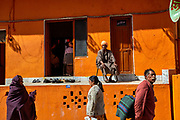 People walking in front of an orange building during the Hindu Festival of Maha Kumbh Mela Haridwar, Uttarakhand, India
