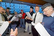 "Passengers braving the waves singing sailors' songs after dinner aboard the ""Lili Marleen"" (luxurious sailing ship of Deilmann Cruises)."