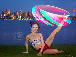 United States, Washington, Seattle, woman with lighted hula hoop and Seattle skyline