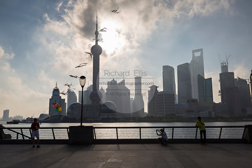 Residents fly a kite early morning on the Bund against the skyline of modern Shanghai, China