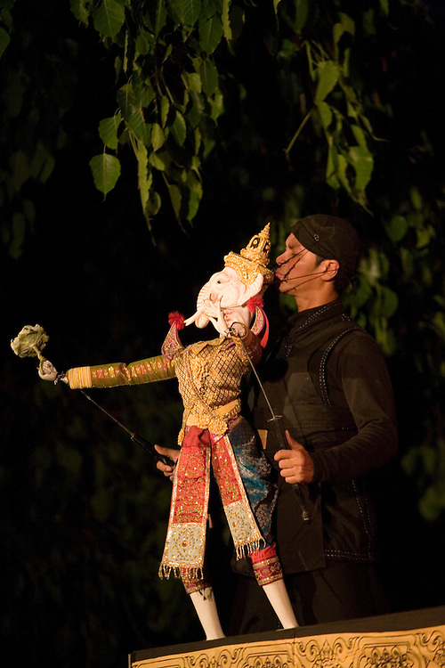Thailand, Bangkok,  Puppet artist performs with Elephant marionette during evening traditional performance in park along Khao San Road
