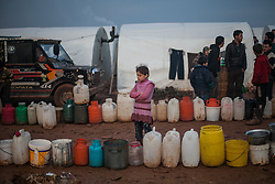 A young girl stands in front of a line of water containers waiting for the truck  which provides water into the camp (twice a day) early morning inside Atmah's refugee camp Idlib province, Syria. Situated along the Turkish border Atmah's refugee camp is considered the biggest refugee camp inside Syria's territory with an estimated number of 13,000 refugees and growing by the day. Is the biggest in an area with another two camps.,000 refugees and growing by the day. Is the biggest in an area with another two camps, Syria, February 5, 2013. Photo by Daniel Leal-Olivas / i-Images.