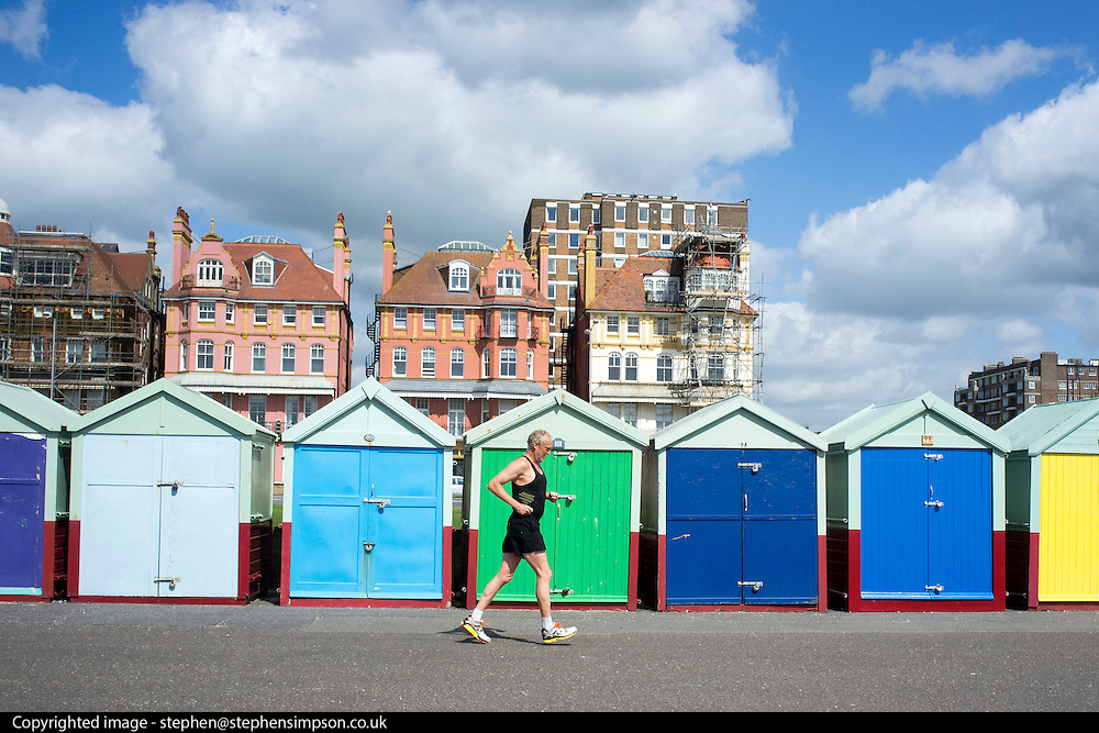 © Licensed to London News Pictures. 18/04/2014. Brighton, UK. A man jogs past beach huts.  People enjoy the  bank holiday sunshine at Brighton today 18th April 2014. Photo credit : Stephen Simpson/LNP