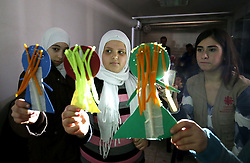 Syrian refugee Mariam Al Azeb, 10, (centre) takes part in a puppet-making workshop during an art therapy class run by psychologist Lina Zaarour (right) at a Caritas centre in the Bekaa Valley region of Lebanon. The classes form part of the psychological care given to the children to help them overcome the trauma of war using arts, crafts and games.