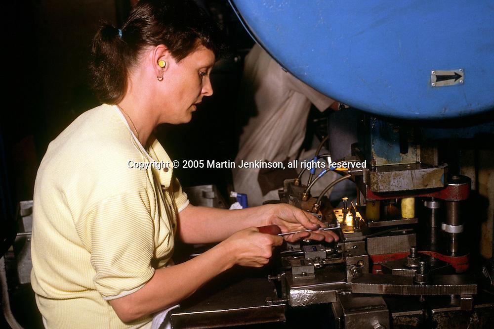 Women wearing earplugs stamping out fork blanks in a cutlery factory in Sheffield ....