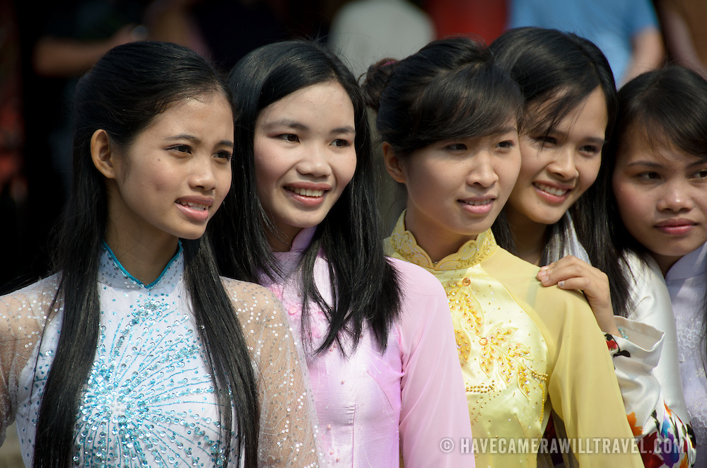 A group of young VIetnamese women in traditional dress pose for photos while visiting the Temple of Literature in Hanoi. The temple was built in 1070 and is one of several temples in Vietnam which are dedicated to Confucius, sages and scholars.