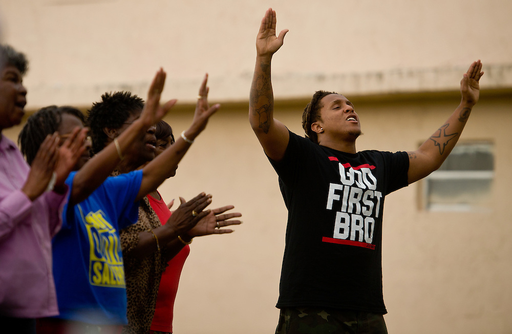 "Rashad ""Blessin"" Johnson, who joins the crowd of worshippers after rapping onstage, listens to Adam Jolley preach at the ""Unity in the Community"" barbecue Feb. 6, 2016, in East Stuart. Jolley, who spent years in prison and now preaches with Fishers of Men Kingdom Ministry, grew up blocks away from the Stuart Police Department-sponsored event in East Stuart. ""I once was someone that was tearing the community down, now I'm here to help restore the community back to peace and unity,"" Jolley said. (XAVIER MASCAREÑAS/TREASURE COAST NEWSPAPERS)"