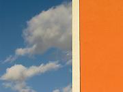 Nuages, ciel bleu et mur orange, Wolke im blauen Himmel mit orangener Hausfassade. © Romano P. Riedo