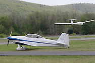 Wurtsboro, NY - A pilot and passenger in a 2001 Mullaney Robert S RV-4 get ready to fly as a glider takes off in the background at the grand reopening of Wurtsboro Airport on May 11, 2008.