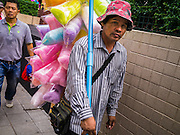 "07 OCTOBER 2012 - BANGKOK, THAILAND:  A Thai cotton candy vendor walks down Sukhumvit Road in Bangkok past Washington Square. Washington Square was a notorious Bangkok ""entertainment district"" at the end of Soi 22 on Sukhumvit Road with several bars, massage parlors and restaurants that appealed primarily to older western male retirees, called ""sexpats"" by Bangkok residents. It was established during the Vietnam War when American servicemen on Rest and Recreation (R&R) leave from Vietnam visited Bangkok for its inexpensive nightlife and liquor. Its reputation was solidified after the war, when American military and intelligence agency retirees settled in Bangkok. Bars in Washington Square have been closing as their leases expire and the area was razed over the summer. The owners of the land are expected to redevelop it into a high rise condominium, office tower or hotel.    PHOTO BY JACK KURTZ"