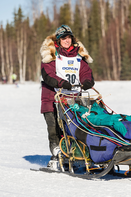 Musher Michelle Phillips competing in the 44th Iditarod Trail Sled Dog Race on Long Lake after leaving the restart on Willow Lake in Southcentral Alaska.  Afternoon. Winter.