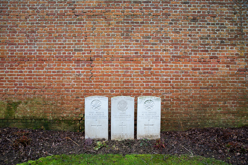 Three headstones placed next to a wall. The centre headstone is an American war grave belonging to Colonel T.J.J. Christian Jr. Faubourg D'Amiens cemetery is the burial site of 2678 identified casualties and a memorial to thousands more from the First and Second World War.  It is looked after and managed by the Commonwealth War Graves Commission in the town of Arras, France. (photo by Andrew Aitchison / In pictures via Getty Images)