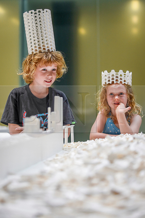 "© Licensed to London News Pictures. 26/07/2019. LONDON, UK. Hunter Tagholm, aged 8 (L), and Willow Beal, aged 5 (R), pose with a Lego crown at the preview of ""The cubic structural evolution project"", 2004, by Olafur Eliasson at Tate Modern.  Exhibited for the first time in the UK, the artwork comprises one tonne of white Lego bricks inspiring visitors to create their own architectural vision for a future city and is on display until 18 August 2019.  The work coincides with the artist's new retrospective exhibition ""In real life"" at Tate Modern on display to 5 January 2020. (Parental permission to photograph obtained). Photo credit: Stephen Chung/LNP"