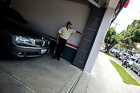A armed security guard stands next to a BMW in the upscale part of town known as Zone 10 in Guatemala City May 19, 2009. In recent days the country of Guatemala is dealing with unrest as the Presidnet Alvaro Colom and Guatemala's business elite are embroiled in a scandal involving money laundering, embezzling government funds and ordering assassinations, following the murder of a prominent lawyer Rodrigo Rosenberg. (Darren Hauck)
