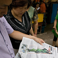 XUZHOU, JULY 22: locals read news about Wendi Deng's life in Xuzhou in the morning paper.