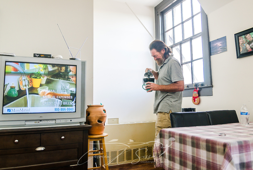 Veteran Darren Dalpiaz relaxes in his new apartment, Nov. 12, 2015, in New Orleans, Louisiana. Dalpiaz, 49, was homeless for 25 years before moving into Sacred Heart Apartments, a community of formerly homeless veterans and non-veterans. UNITY, a 60-agency coalition, provides housing and services for people who are homeless. Dalpiaz was the last of 227 homeless veterans housed by UNITY. (Photo by Carmen K. Sisson/Cloudybright)