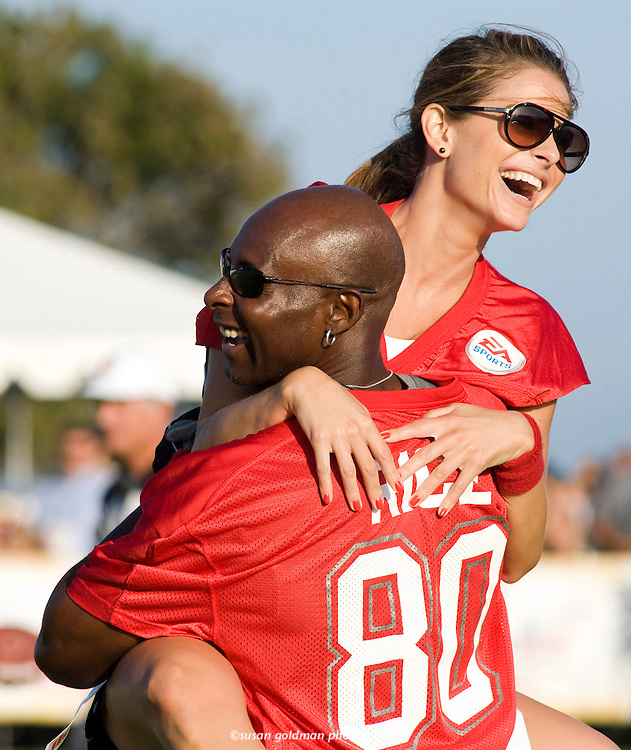 Jerry Rice, Pro Football Hall of Famer, lifts Maria Menounos, actress and television host, celebrating their team's touchdown in the EA SPORTS Madden NFL 11 Pigskin Pro-Am, in Malibu, Calif. Photo/EA SPORTS, Susan Goldman.