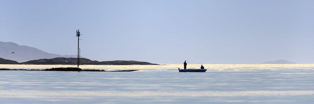 Two persons in a small boat enjoy a nice sunny evening with fishing | To personer i en liten fritidsbåt koser seg med fisking i kveldssolen.
