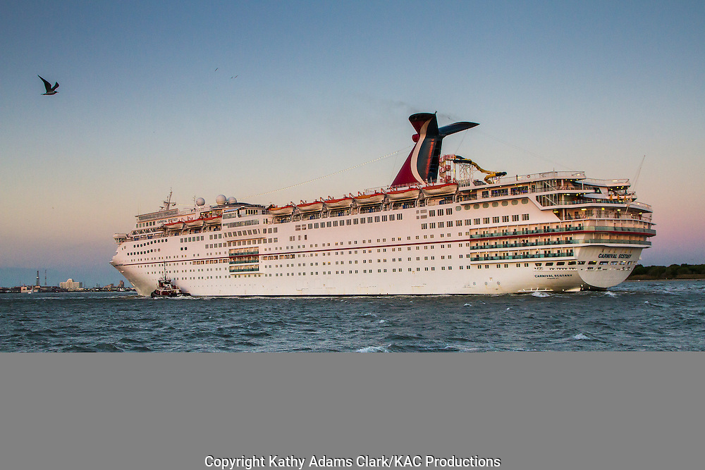 Carnival Ecstasy cruise ship escorted through Galveston harbor by tugboat