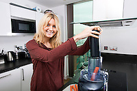 Portrait of young blond woman using juicer for juicing carrots in kitchen