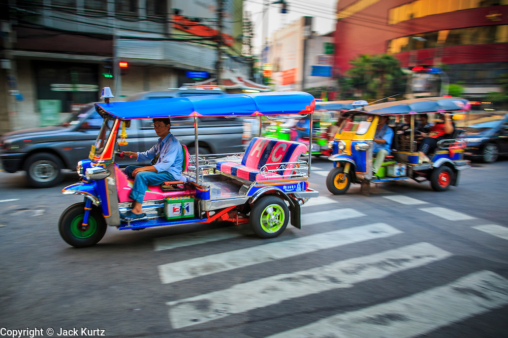 07 DECEMBER 2012 - BANGKOK, THAILAND:  Tuk-tuks (three wheeled taxi) in traffic in the Chinatown section of Bangkok, Thailand. Chinatown is the entrepreneurial hub of Bangkok, with thousands of family owned businesses selling wholesale merchandise in everything from food like rice, peanuts and meats, to dry goods like toys and shoes. Tuk-tuks are three wheeled taxis that use a motorcycle engine. In one form or another they are common in much of Asia.     PHOTO BY JACK KURTZ