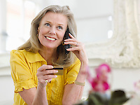 Woman holding credit card using phone in living room portrait