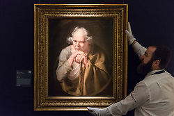 "© Licensed to London News Pictures. 29/11/2019. LONDON, UK. A technician presents ""Study of a Philosopher"", late 1760s, by Joseph Wright of Derby (Est. GBP200-300k) at the preview of Old Masters sales at Sotheby's, New Bond Street.  Works will be offered for sale on 4 and 5 December.  Photo credit: Stephen Chung/LNP"