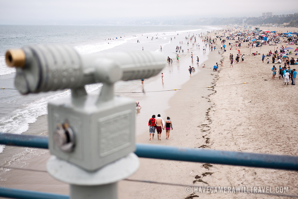 A coin operated telescope on Santa Monica pier overlooking the crowds of people on the beach and surf of Santa Monica. The shot has a very narrow field of focus on the people and beach, with the telescope blurred.