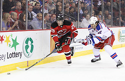 Mar 6; Newark, NJ, USA; New Jersey Devils defenseman Mark Fayne (29) skates with the puck while being defended by New York Rangers center Brian Boyle (22) during the first period at the Prudential Center.