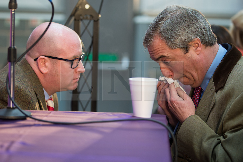 © Licensed to London News Pictures . 23/03/2015 . Middleton , UK . Paul Nuttall and Nigel Farage talk as Nigel Farage blows his nose . UKIP leader Nigel Farage , Deputy Leader Paul Nuttall and Economics Spokesman Patrick O'Flynn announce UKIP's economic policy at Concept Metal Products and Co Ltd in Middleton , Lancashire . Photo credit : Joel Goodman/LNP