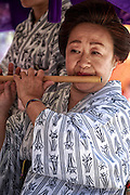 A woman plays a wooden flute during the Sanja Matsuri. Sanja Matsur (Three Shrine Festival), is an annual Shinto festival held in Tokyo. The earliest form of the festivals dates back to the 7th century CE and is held in honor of Hinokuma Hamanari, Hinokuma Takenari and Hajino Nakatomo, the three men who established and founded Sensō-ji temple. Sanja Matsuri is held on the third weekend of every May at Asakusa Shrine. Its  parades revolve around three mikoshi (three portable shrines referenced in the festival's name), as well as traditional music and dancing.
