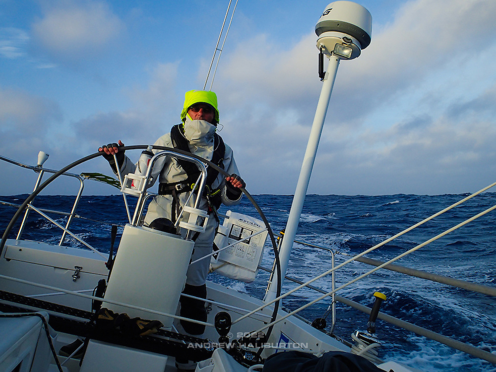"Scott Campbell at the helm of J46 ""Riva"" on a rough Pacific Ocean in gale-force wind, racing to Hawaii in the 2070 nautical mile Pacific Cup 2016 ocean race."