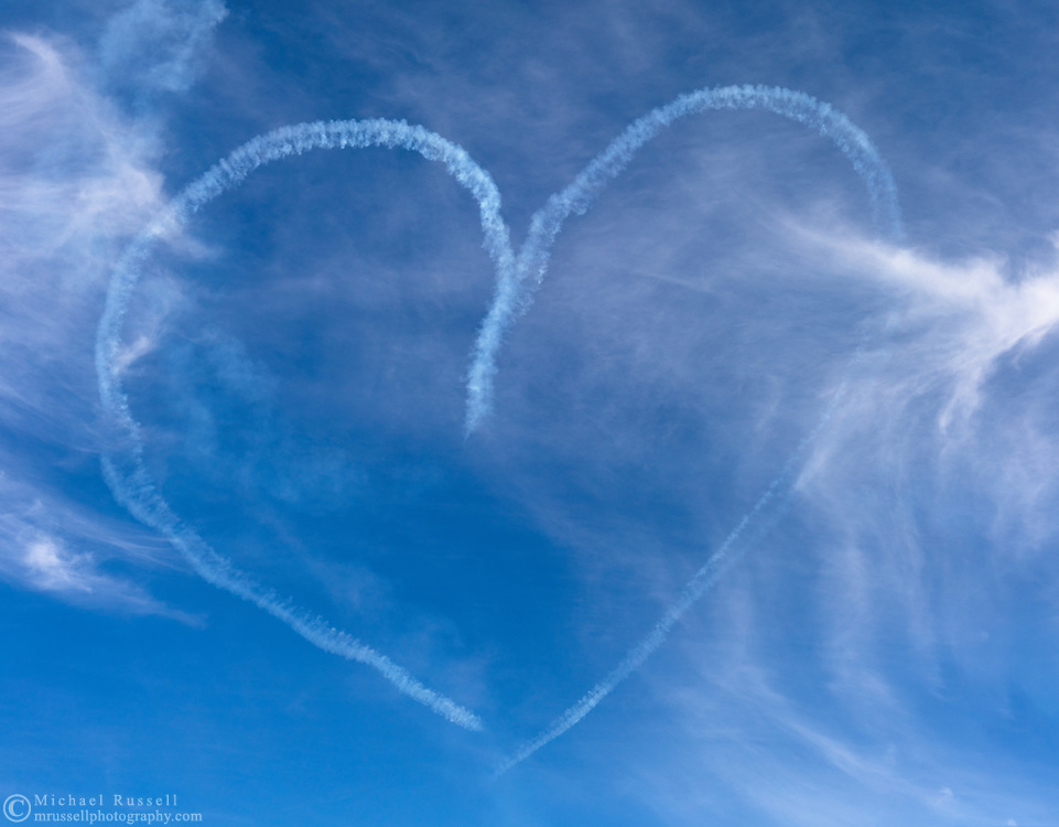 Two Canadian Forces Snowbirds draw a heart in the sky during an aerobatic manoeuvre with smoke.  The Snowbirds are also known as the 431 Air Demonstration Squadron and fly the Canadair CT-114 Tutor jet. Photographed during the Canada 150 celebrations in White Rock, British Columbia, Canada.