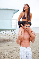 Young Couple Riding Piggyback on Beach