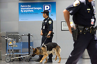 SAN FRANCISCO, CA - JULY 3 :  San Francisco police officer Carlos Cordova and his dog Fax patrol the ticketing area of the International Terminal at the San Francisco International Airport on July 3, 2007 in San Francisco, California. Security threat level was raised to orange as the nation gets ready for the Fourth of July holiday.  (Photograph by David Paul Morris)