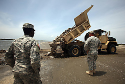 13 May 2010. Elmer Island, Lafourche Parish, Louisiana. <br /> Louisiana National Guard of the 922nd Horizontal Engineer Company, 769th Engineer Battalion fight a losing battle against mother nature as they battle against the strong currents to close the inland waterways from the ocean now depositing oil from the Deepwater Horizon catastrophe on the beaches. <br /> Photo credit; Charlie Varley/varleypix.com