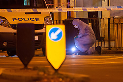A forensics investigator examines the road outside the station at the scene where a seventeen-year-old , the second teenager in less than 24 hours, was stabbed and died outside Clapham South Underground Station. Clapham South, London, November 02 2018.
