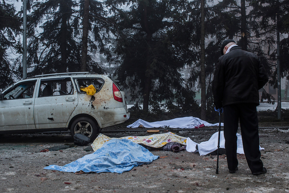 DONETSK, UKRAINE - JANUARY 30, 2015: An investigator looks at the bodies of four people who were killed when a rocket struck the parking lot outside a center where humanitarian aid was being distributed in Donetsk, Ukraine. A fifth person was killed in a parked car, and at least two others died in a separate shelling nearby. CREDIT: Brendan Hoffman for The New York Times