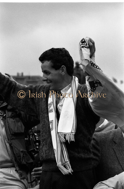 Stephen Roche, Tour de France Winner.  (R61)..1987..26/27 .07.1987..07. 26/27.1987..26/27th July 1987..Tour de France Winner Stephen Roche, the first Irishman to do so , was feted on his arrival back in Dublin. The people of Ireland descended on Dublin to throng the streets as they congratulated Stephen on his momentous achievement...Image shows Stephen Roche waving to the crowds from the open topped CIE bus as he paraded through the streets of Dublin.