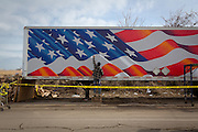 Scott Lobaido, a mural painter, put an American flag on a trailer outside the Guyon Rescue relief center on Mill Road. The trailer contained work boots donated by the Keen footwear company; relief center volunteers doled them out to storm-hit residents.