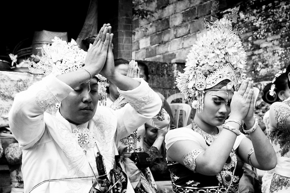 Yulie the bride during the Balinese Wedding Ceremony .<br /> <br /> The main part of this wedding ceremony is held in the groom's house, to welcome the bride to become a part of the groom's family.<br /> There are several parts in this Ceremony, which is called Sudi Widani.<br /> Because the bride has a different religion and becomes Hindhu this is the ceremony for the bride and is witnessed by the Local Leader in the village, a Holy man and by family of the bride and family of the groom.<br /> <br /> After the bride has been through this Ceremony than there is the next Ceremony, which is the Mekala-Kalaan,<br /> which is the bride's and groom's top ceremony.<br /> <br /> In this Ceremony they both have to do a few steps and will be guided by the priest and witnessed by the family and which is followed by praying in the temple in the house.<br /> This is Final step of the Wedding Ceremony for Hindhus in Bali.<br /> <br /> After these Ceremonies their is a  Receiption in the groome's house for family and relatives and some close friends who witnessed the marriage.<br /> <br /> KlungKung, Bali<br /> 24 December 2012<br /> &copy;Ingetje Tadros