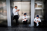 Hong Kong, China - Men and woman smokes and checks their mobile phone on a street in Hong Kong during a work break on April 30, 2018