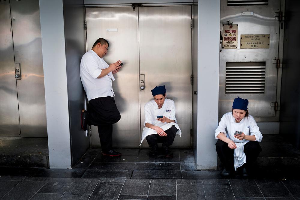 Hong Kong, China - Men and woman smokes and checks their mobile phone on a street in Hong Kong during a work break on April 30, 2018Hong Kong, Chine - Des hommes et des femmes fument et vérifient leur téléphone portable dans une rue de Hong Kong pendant une pause le 30 avril 2018.