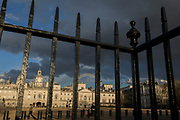 The capital's landmark, Horseguards is seen through railings in St. James's Park, on 21st March 2017, in London, England. Horse Guards is a large Grade I listed historical building in the Palladian style in London between Whitehall and Horse Guards Parade. The first Horse Guards building was built on the site of the former tiltyard of Westminster Palace during 1664. It was demolished during 1749 and was replaced by the current building which was built between 1750 and 1753 by John Vardy after the death of original architect William Kent during 1748.