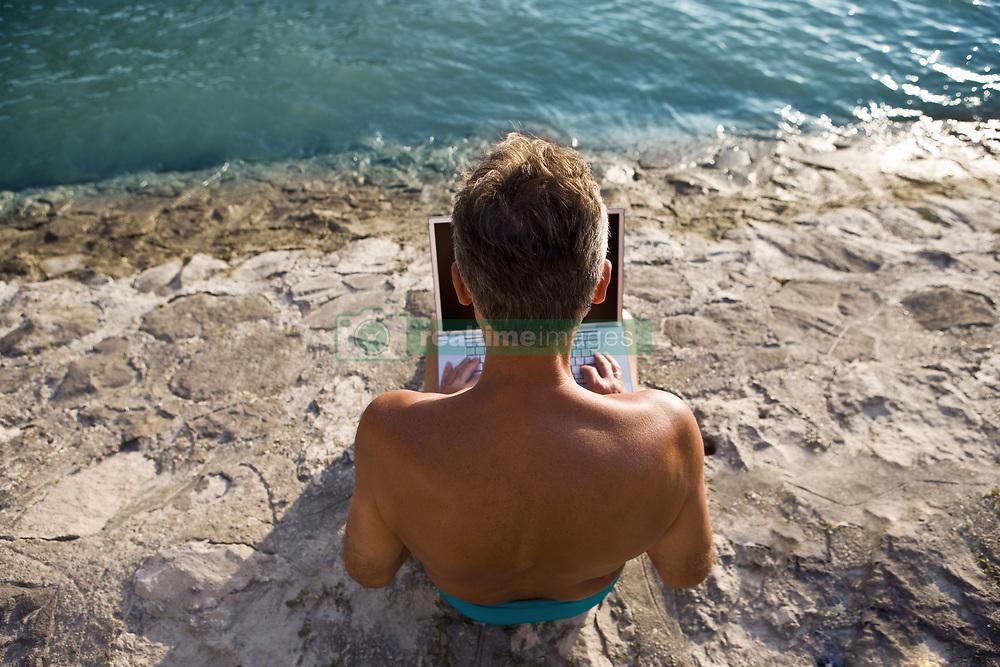 Aug. 25, 2007 - Man using laptop by river. Model Released (MR) (Credit Image: © Cultura/ZUMAPRESS.com)