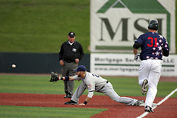 12 August 2011: With the delivery of the ball to first baseman Kevin Smith, Mark Samuelson ends his turn at bat during a game between the Rockford River Hawks and the Normal Cornbelters at the Corn Crib in Normal Illinois.