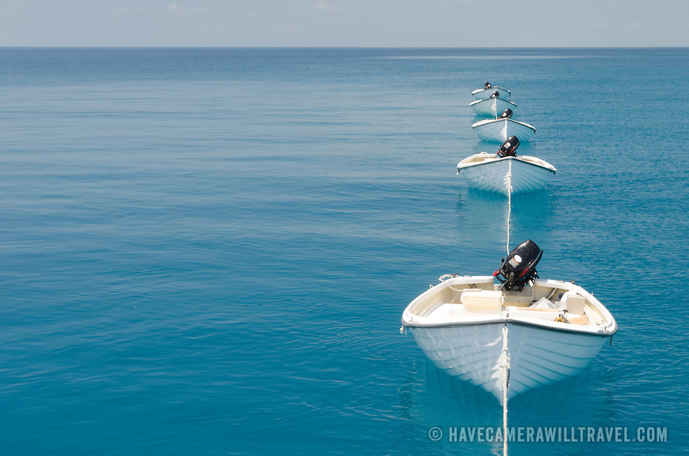 A line of small dories strung behind a larger boat on the water of Swains Reef on Australia's Great Barrier Reef.