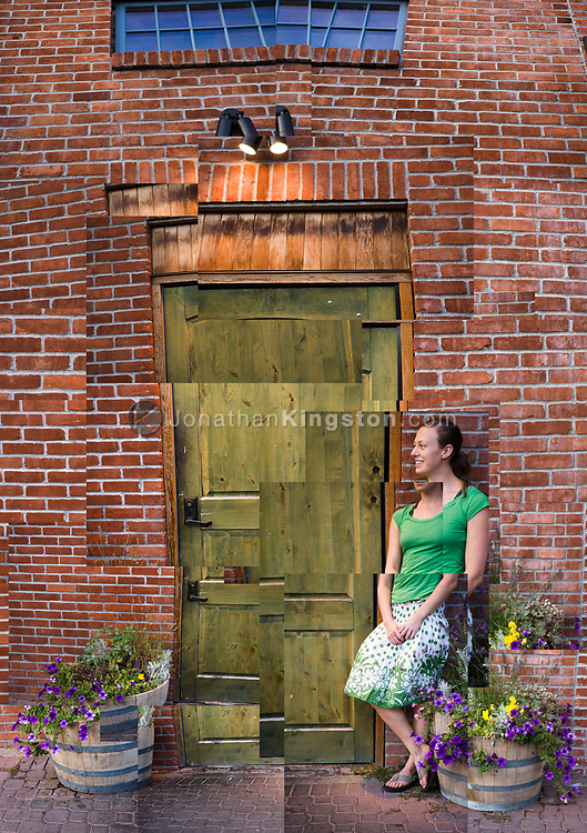 Young woman standing next to a green door in Bend, Oregon. (multi image composite) (Model Released)