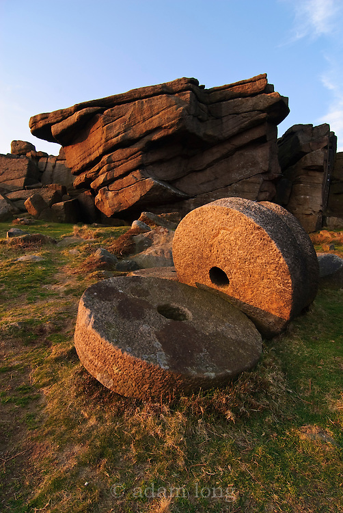 Abandoned Millstones lie scattered below parts of Stanage in The Peak District